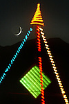 The cresent moon set behind the Black Rock mountains range as neon art at High Rock Canyon lite up the sky during the Burning Man Festival. .