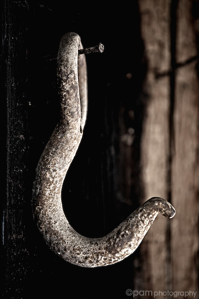 Black and white still life of old hook in blacksmith shop