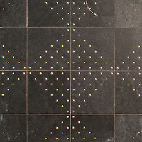 Yorke, a waterjet stone mosaic, shown in honed Orpheus Black and Brass studs, is part of the Bright Young Things™ collection by New Ravenna.