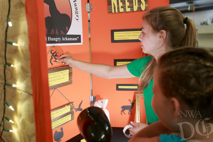 NWA Democrat-Gazette/CHARLIE KAIJO Kinley Russell 9 and Faith Fritch 15 of Bentonville (from right) set up their 4-H club educational presentation board, Saturday, August 4, 2018 at the Benton County Fairgrounds in Bentonville. Their presentation is called Arkansas Hunters Feeding the Hungry. They want to encourage people to donate deer and other game to help feed those in need of food. Meat is hard to get in food pantries said Fritch. Of the 200,000 hunted game in Northwest Arkansas, only one percent is turned in to food pantries according to a stat on their board. <br /><br />Vendors prepared their booths ahead of the Benton County Fair which is set to begin August 7.