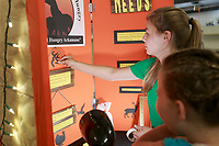 NWA Democrat-Gazette/CHARLIE KAIJO Kinley Russell 9 and Faith Fritch 15 of Bentonville (from right) set up their 4-H club educational presentation board, Saturday, August 4, 2018 at the Benton County Fairgrounds in Bentonville. Their presentation is called Arkansas Hunters Feeding the Hungry. They want to encourage people to donate deer and other game to help feed those in need of food. Meat is hard to get in food pantries said Fritch. Of the 200,000 hunted game in Northwest Arkansas, only one percent is turned in to food pantries according to a stat on their board. <br />