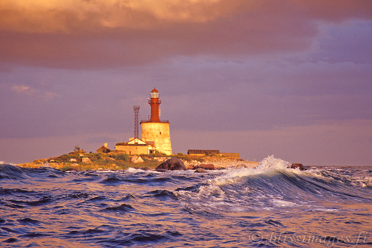 A wave crests on the rocky approaches to Keri Island Lighthouse, Estonia.