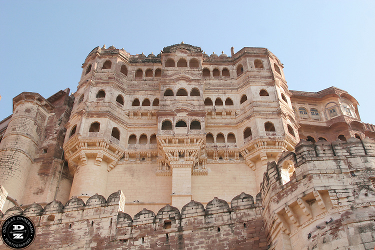 The facade of Meherangarh, the fort of the maharaja of Jodhpur, is an imposing fort sitting atop of a125 meter high hill in the center of the city.  Meherangarh dominates the skyline of the city of Jodhpur, India, which sprawls below the fort as a mass of cubist shapes, most painted blue.  Photograph by Douglas ZImmerman