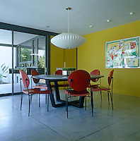 A contemporary artwork mounted on the wall of the dining room echoes the red and yellow used in its decoration