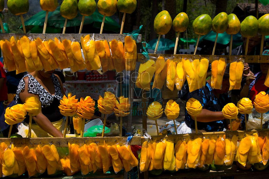 Fruit for sale as people visit Iglesia San Bartolomé Becerra in Antigua, Guatemala two days before the Procesión de Jesús Nazareno de La Caída from. Each weekend during Lent features a procession by a different church, culminating in Semana Santa, or Holy Week, one of the largest Easter commemorations in Latin America.