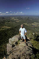 Australia, Queensland, Glasshouse Mtns., man atop Mt. Beerwah, Mt. Coonowrin in background