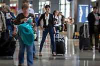 Young pretty stylish woman with suitcase carry-on luggage stands in the terminal at the Austin–Bergstrom International Airport (ABIA).