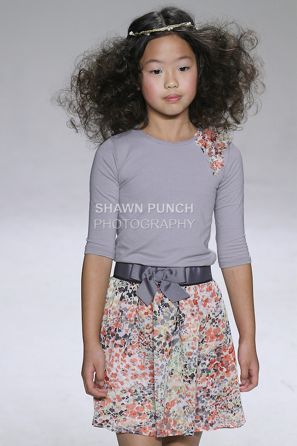 Young model walks runway in an outfit from the Charm Spring Summer 2015 collection by Rany Mendlovic, during Kids Fashion Week in New York City, on October 19, 2014.
