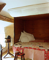 A box bed with a traditional Welsh quilt fits snugly into this tiny bedroom