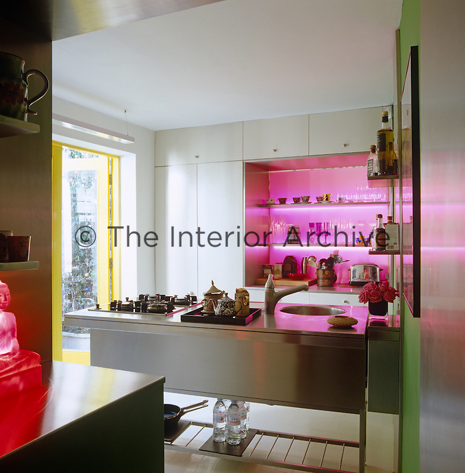 Backlit pink acetate and Lucite create a bar-like effect in this contemporary kitchen