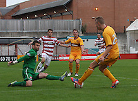 Goalkeeper Kevin Cuthbert spreads himself to stop Lee Erwin in the Hamilton Academical v Motherwell friendly match played at New Douglas Park, Hamilton on 24.7.12..