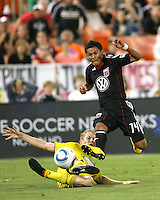 Andy Najar #14 of D.C. United avoids a sliding tackle from Kevin Burns #15 of the Columbus Crew during an MLS match at RFK Stadium on September 4 2010, in Washington DC. Columbus won 1-0.