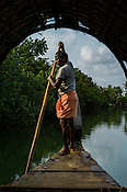 A boatman rows the boat through the backwaters in Kerala, India.
