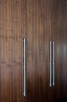 Simple handles of stainless steel echo the long lines in the design of some built-in wardrobes
