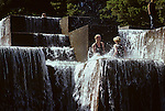 Downtown waterfall park with teens in water splashing and having fun afternoon Portland Oregon State USA