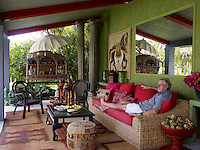 Swedish designer Lars Bolander photographed relaxing on a rattan sofa on the covered terrace of his Florida home