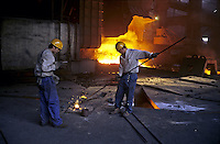 Two workers test iron in Benxi Iron and Steel Group in Liaoning. China's second-largest steelmaker Anshan Iron & Steel Group has merged with smaller rival Benxi Steel Group to create a company with capacity that will match the mainland's biggest steelmaker, Shanghai Baosteel Group..22 Aug 2005