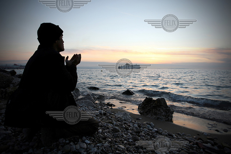 Greece/ Patra / A man from Afghanistan praying on the beach near the port of Patras.The port of Patras is one of the biggest crossing points to continental Europe. Thousands of the immigrants in Greece gather in the country's biggest ports, in hopes of stowing away on one of the trucks loaded onto Italy-bound ships and ferries. Day and night, they sprint after the trucks as they pass through the gates, trying to latch onto the doors or crawl into the wheel wells. During the last years, in their effort to continue their journey, dozens have been found dead died suffocation inside the trucks.  Giorgos Moutafis