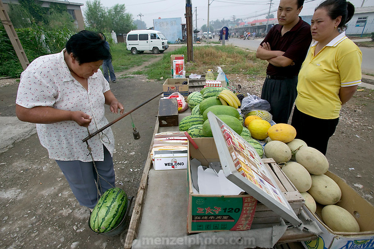 Visiting a fruit vendor in another nearby town, Li Jinxian and Cui Haiwang watch as a watermelon they are buying is weighed. (Supporting image from the project Hungry Planet: What the World Eats.) The Cui family of Weitaiwu village, Beijing Province, China, is one of the thirty families featured, with a weeks' worth of food, in the book Hungry Planet: What the World Eats.