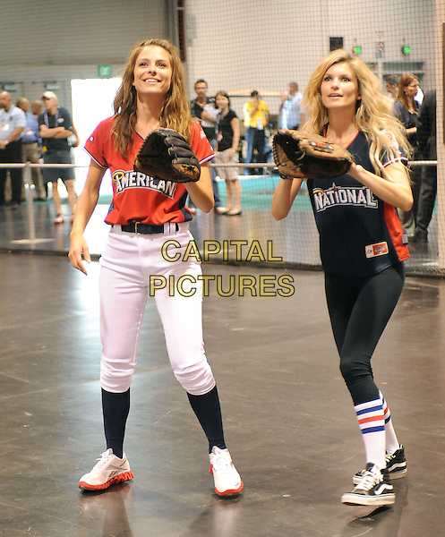 MARIA MENOUNOS & MARISA MILLER.At the MLB All Star Fanfest Batting Practice held at The Anaheim Convention Center , the precursor to The All Star Legends Celebrity Softball game in Anaheim, California, USA..July 11th, 2010.full length red black top baseball mitt glove socks white trousers leggings catch catching .CAP/RKE/DVS.©DVS/RockinExposures/Capital Pictures.