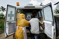 55 yearold Jariath Sesay, who is severely ill with ebola-like symptoms is helped by a man in PPE (personal protection equipment) into an ambulance outside her home in Kissy Town to a treatment facility. Her son, who has been nursing her, is also helping her but has no protective clothing.