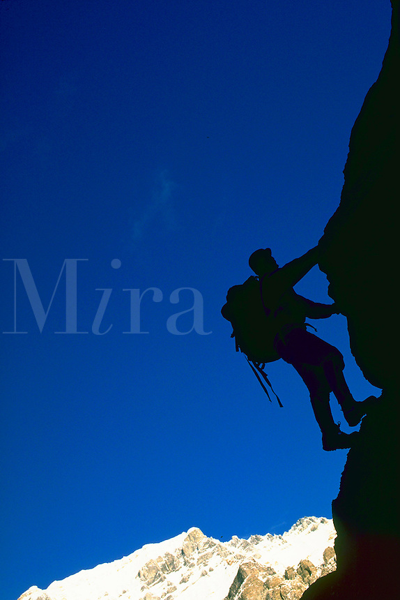 Silhouetted man scaling a rock face in Banff National Park. Banff National Park is in the Canadian Rockies.