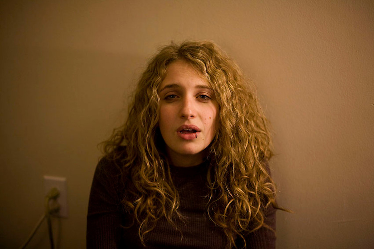 A girl sits in a room of an apartment building while smoking marijuana in southeastern Ohio.