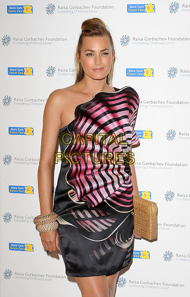 YASMIN LE BON .attending The Raisa Gorbachev Foundation Gala, Stud House, Hampton Court Palace, London, England, UK,.5th June 2010..half length black dress pink striped one shoulder fan strapless cut out bangles bracelets clutch bag .CAP/BEL.©Tom Belcher/Capital Pictures.