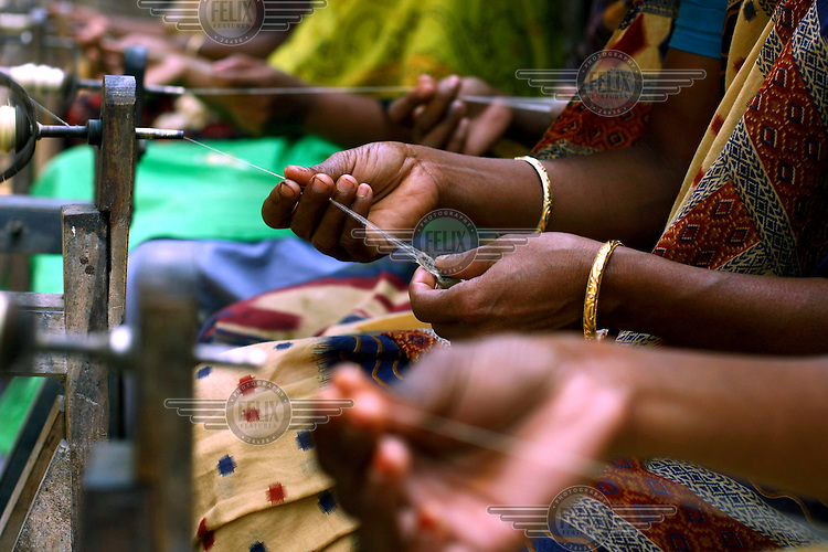 Sericulture workers spin silk from silkworm cocoons using a spinning wheel known as a 'charka' to yield fine thread...
