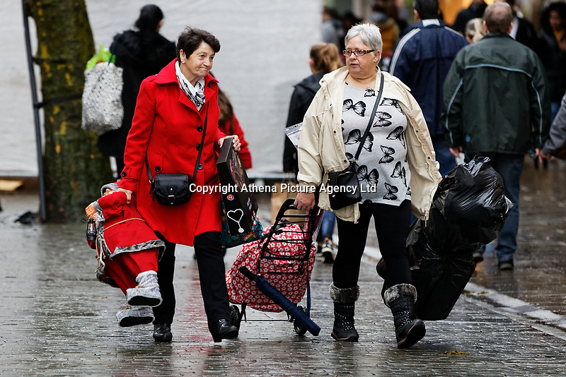 Two women with their shopping, including a Santa, join other last minute Christmas shoppers in Oxford Street, in the city centre of Swansea, Wales, UK. Sunday 24 December 2017