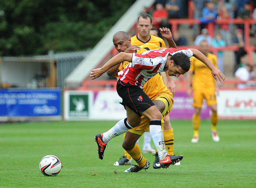 Exeter City's Craig Woodman is tackled by Newport County's Chris Zebroski<br /> <br /> Photo by Ashley Crowden/CameraSport<br /> <br /> Football - The Football League Sky Bet League Two - Exeter City v Newport County - Saturday 21st September 2013 - St James Park - Exeter<br /> <br /> &copy; CameraSport - 43 Linden Ave. Countesthorpe. Leicester. England. LE8 5PG - Tel: +44 (0) 116 277 4147 - admin@camerasport.com - www.camerasport.com