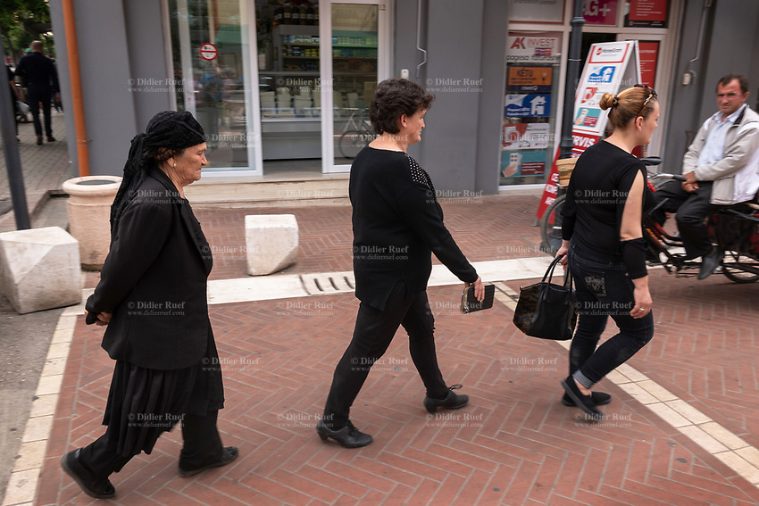 Albania. Tirana. Grandmother, mother and daughter, all from the same family, walk in the town center. Tradition to modernity in the way they dress. Black for all, a scarf to cover the hair and a long dress for the elderly woman and jeans and sleeveless cloth for the youngest. Tirana is the capital and most populous city of the Republic of Albania. The city is also the capital of the surrounding county of Tirana, one of 12 constituent counties of the country. 20.5.2018 © 2018 Didier Ruef