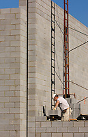02/22/07:  A construction worker lays cement cinderblock in place to build a wall during construction/expansion of a Charlotte-area shopping center. Charlotte, NC, is one of the country's fastest-growing cities. ..By Patrick Schneider- Patrick Schneider Photography.