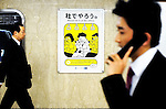 Businessmen walk past a poster requesting commuters refrain from talking on their mobile phones on trains hangs at an underground station in Tokyo, Japan. The Japanese are well known for their civility and politeness,  but a recent governmental campaign to clamp down on lewd behavior that may inconvenienc others -- including talking on cell phones and applying makeup while commuting on a train -- was fueled by a decline in everyday etiquette and manners.