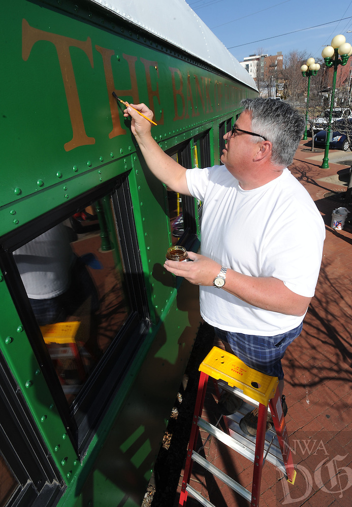 NWA Democrat-Gazette/ANDY SHUPE<br /> Eric Snodgrass, owner of Snodgrass Signs in Fayetteville, puts the finishing touches Wednesday, Feb. 8, 2017, on gold lettering at the Bank of Fayetteville's location at West Avenue and Dickson Street in Fayetteville. The location is housed in a former passenger train and caboose which has undergone an exterior renovation that began in the fall.