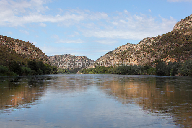 Ebro river with mountains on both banks, Tarragona, Spain. In this region the river is near the end of its course, passing through gorges and mountainous scenery before flowing out through the Ebro Delta into the Mediterranean Sea. Picture by Manuel Cohen