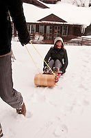 A couple enjoys sledding at the Keweenaw Mountain Lodge in Copper Harbor Michigan in winter.