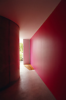 The entrance hall has a bright red wall and has to accommodate the concrete support for the building