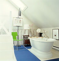 An attic bathroom is furnished with a contemporary take on a vintage bath and a lime green chair