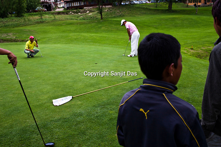 40 year old Yougs Dorji with a zero handicap putts the ball on the greens at the Royal Thimphu Golf Course in Thimphu, Bhutan. Photo: Sanjit Das/Panos