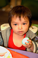 Toddler age 3 holding dyed Easter egg at church  soup kitchen.  Minneapolis Minnesota USA