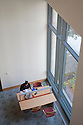 A high angle view of a woman studying at a desk by a large window. The San Mateo Public Library integrates significant green building practices and achieved LEED Silver certification. Green features include extensive daylighting, efficient underfloor air supply, venting windows, low VOC materials, native plant landscaping, and much more. San Mateo, California, USA