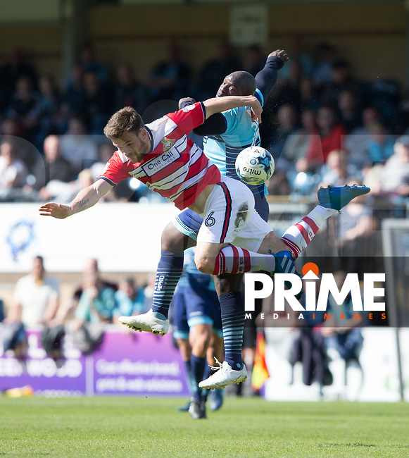 Adebayo Akinfenwa of Wycombe Wanderers goes for a header against Andy Butler of Doncaster Rovers during the Sky Bet League 2 match between Wycombe Wanderers and Doncaster Rovers at Adams Park, High Wycombe, England on 22 April 2017. Photo by James Williamson / PRiME Media Images.