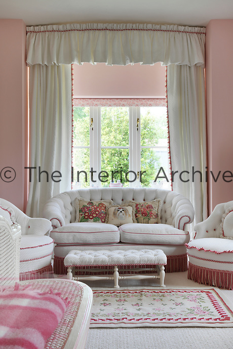 A dog cushion forms the centre piece of a suite of red and white chairs and a sofa in a pink bedroom