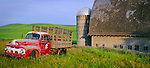 Whitman County, WA<br /> Vintage red Ford flatbed truck in front of weathered barn and silo in summer, Palouse Country