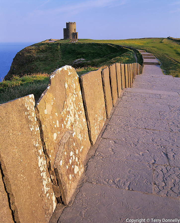County Clare, Ireland                  Fence and pathway of stone slabs on the rim of the Cliffs of Moher leading to O'Brien's Tower on the headland's point