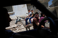 SYRIEN, 07.2014, Koreen (Provinz Idlib). Leben ohne Zentralregierung: Teenager reiten auf Pferden durch die Strassen vorbei an Autos und Motorraedern. | Life without a central government: Teenage boys ride horses in the streets passing motorbikes and cars.<br /> © Timo Vogt/EST&OST