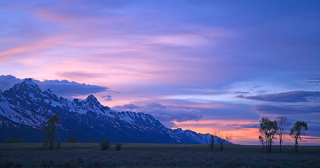 THE SUN SETS BEHIND THE GRAND TETON MOUNTAIN RANGE NEAR JACKSON, WYOMING
