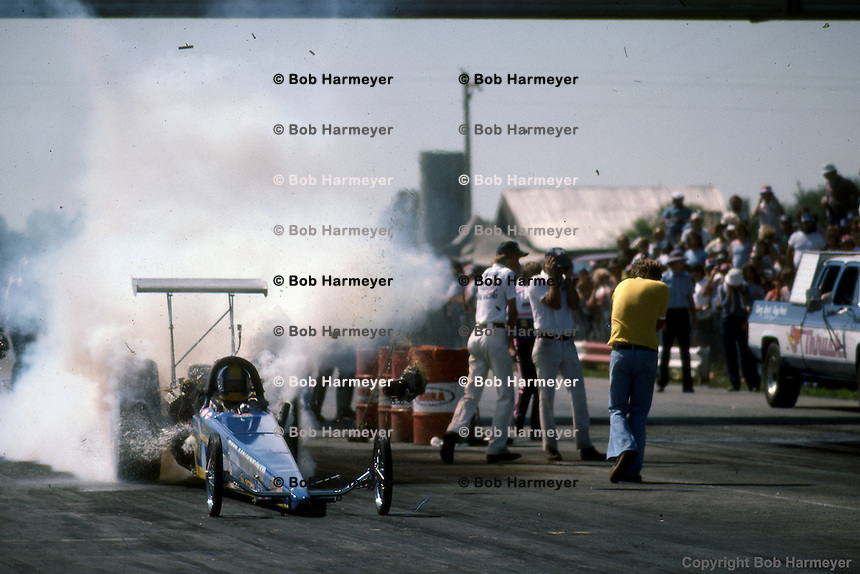 INDIANAPOLIS, INDIANA: An engine explodes on the starting line during the 1976 NHRA US Nationals drag race in Indianapolis, Indiana.