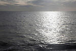 Sunshine falling on expanse of grey sea water, North Sea, Suffolk, England